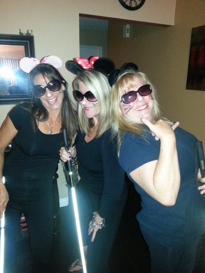 PHoto of d myTwo girlfriends, Ursula and Robin, and myself dressed up in sunglasses, mouse ears, Whiskers, and Laughing holding white canes.