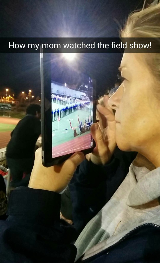 Image: A photo of me holding and iPad up to my face as I view the marching band on the field through the camera.