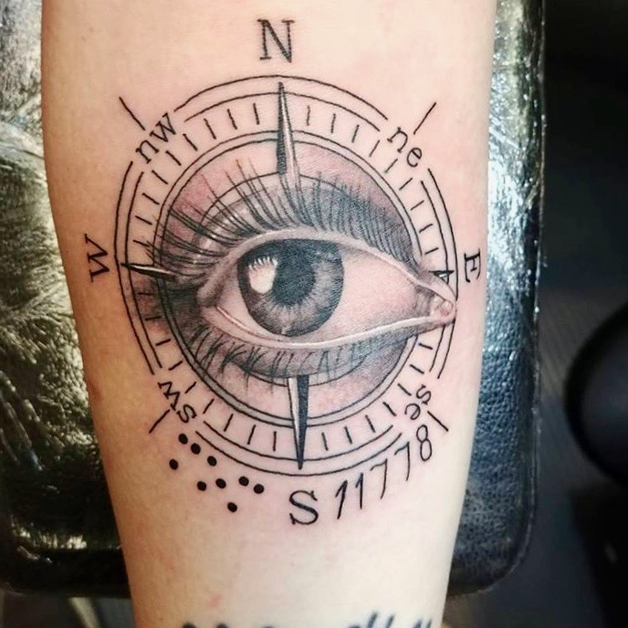 Image: Picture of Alison's tattoo. It is an Intricate black illustration of a compass. In the middle Of the compass is an eye with long lashes. The compass is marked with letters representing North, south, east, and west.